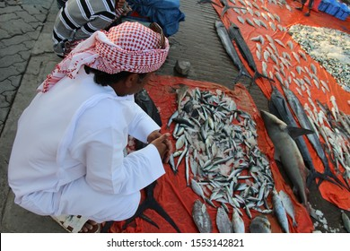 Dibba, Musandam / Oman - Circa December 2018: An Arab man wearing the traditional white robe, the dishdasha, and the headdress, the keffiyeh, is looking at the catch of the day at the fish market.