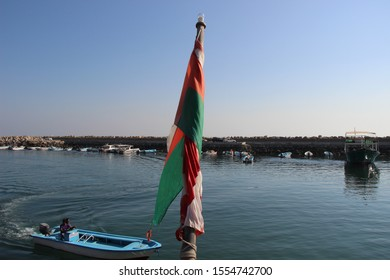 Dibba, Musandam / Oman - Circa December 2018: the Omani flag at the forefront, a local fisherman in the back in his wooden boat at the port of Dibba.
