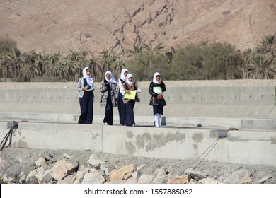 Dibba, Musandam / Oman - December 2018: A group of young Omani Muslim girls happily walking back home from school, their notebooks in hand, chatting with each other.