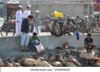 Dibba, Musandam / Oman - December 2018: South Asian migrant workers taking a short break, squatting on rocks, with young Omani boys peering at the content of a bag that one of them is holding.