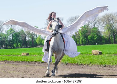 DIBRIVKA, UKRAINE – 1 MAY, 2018: A girl with white wings on horseback during the show competitions in equestrian sport in Dibrivsky Horse Plant