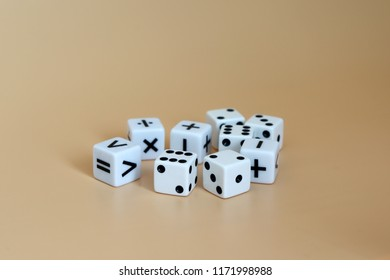 Dice and arithmetic operation symbol cubes on a soft brown background.