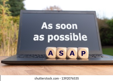 """Dice form the abbreviation """"ASAP"""". Dice placed on a Notebook. The text """"as soon as possible"""" is written on the display."""