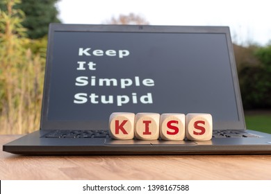 """Dice form the abbreviation """"KISS"""". Dice placed on a Notebook. The text """"Keep it simple stupid"""" is written on the display."""