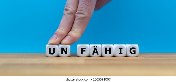 "Dice form the German word ""UNFÄHIG"" (""incapable"" in English) while two fingers push the letters ""UN"" away in order to change the word to ""FÄHIG"" (""capable"" in English)."