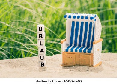 """Dice form the German word """"URLAUB"""" (""""holiday"""" in English) next to a beach chair. - Shutterstock ID 1445078600"""