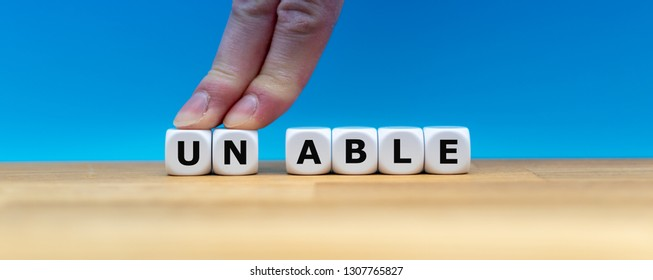 "Dice form the word ""UNABLE"" while two fingers push the letters ""UN"" away in order to change the word to ""ABLE""."