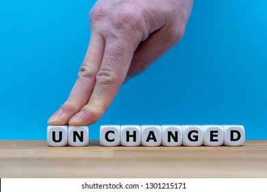 "Dice form the word ""UNCHANGED"" while two fingers push the letters ""UN"" away in order to change the word to ""CHANGED""."