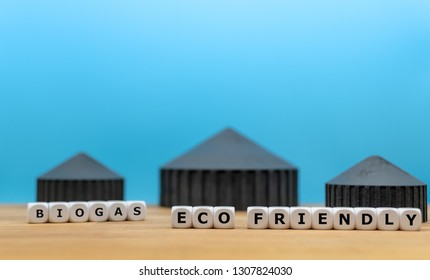 """Dice form the words """"BIOGAS"""", """"ECO"""" and """"FRIENDLY"""" in front of a model of a biogas plant."""