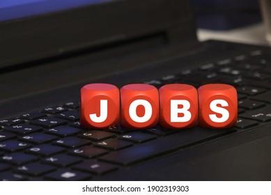 Würfel mit Buchstaben JOBS auf einer Tastatur - Jobsuche und Online-Anwendung