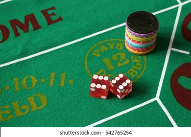 Dice on crap layout showing 12, stack of multi colored chips, 12 pays double. Boxcars Casino gambling green.