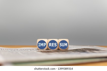 """Dice on a newspaper form the German word """"Impressum"""" (""""Imprint"""" in English)."""