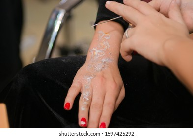 dice over his hands . He puts a dice on his hand . puts a red varnish and henna in the girl's hand . The girl has a red varnish in her hand.
