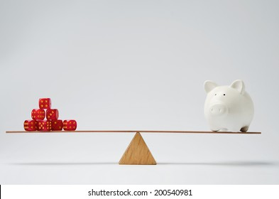 Dice stack and piggy bank balancing on a seesaw