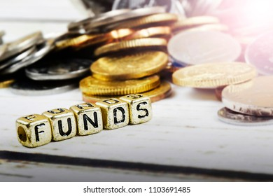 Dice with word FUNDS and coins on wooden background. Funding and business concept. Shallow DOF.