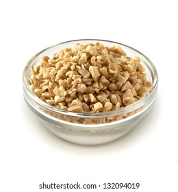Diced hazelnuts or filberts in glass bowl isolated on white background
