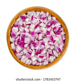 Diced red onions in wooden bowl. Cut cubes of onion cultivar Allium cepa, with purplish red skin and white flesh tinged with red. Closeup, from above, on white background, isolated, macro food photo.