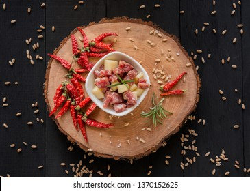 diced salami and cheese bowl on a wooden plate with a tree trunk with hot peppers and spelled