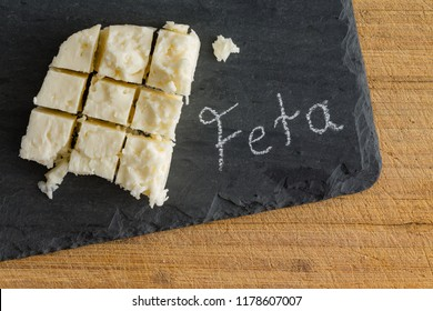 Diced slab of traditional semi-soft crumbly Greek feta cheese on a slate board with handwritten text - Feta - alongside viewed from above
