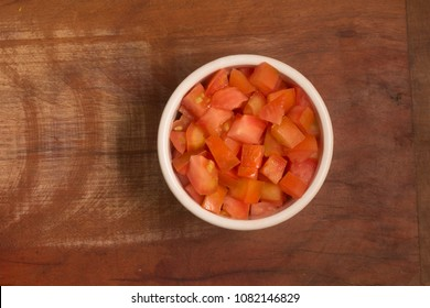 Diced tomatoes in a bowl over a wooden table