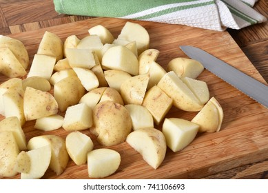 Diced yukon gold baby potatoes on a cutting board