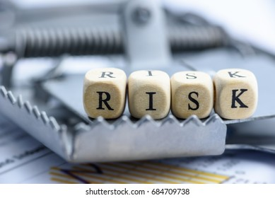 "Dices are arranged in a word ""RISK"" on a rat trap. Concept of risk management which a key component is risk assessment, involves the determination of the risk surrounding a business or investment."