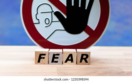 """Dices form the word """"FEAR"""" infront of a stop sign"""