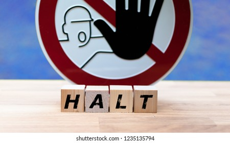"""Dices form the word """"HALT"""" infront of a stop sign"""