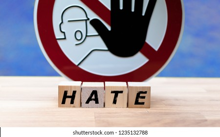 """Dices form the word """"HATE"""" infront of a stop sign"""