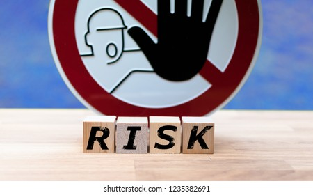 """Dices form the word """"RISK"""" infront of a stop sign"""