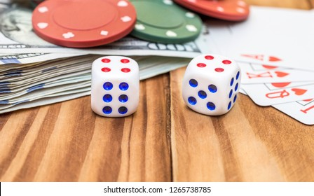 Dices with playing cards, poker chips and money on the wooden background. Close up.