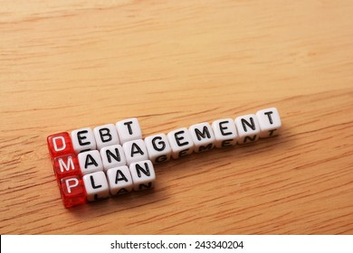 dices with word DMP debt management plan on wooden  background