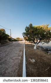 Dichotomy by a white line on a road in a Greek fishing village