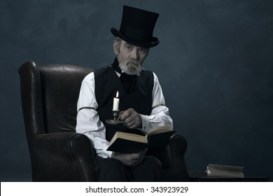 Dickens Scrooge Man Sitting in Chair with Book by Candlelight.