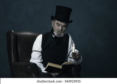 Dickens Scrooge Man Sitting in Chair Reading Book by Candlelight.