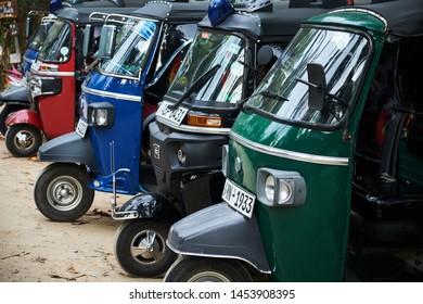 Dickwella, Sri-Lanka - January 26, 2019: Tuk-tuk with Siren Popular Oriental Transport. Motor Rickshaw Tricycle Model Automobile Standing in Row. City Car for Transportation Passenger or Cargo