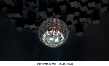 Dico ball on black cube style ceeling in nightclub with striped white and black walls lit by spotlight, party and nightlife entertainment industry