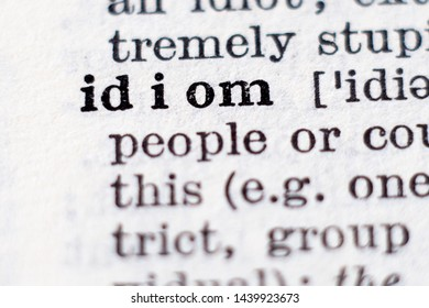 Dictionary definition of word idiom, selective focus.
