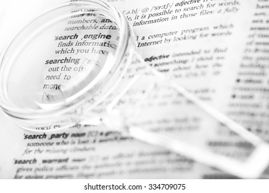 Dictionary definition of the word search, searching, search engine optimization and magnifying glass close-up