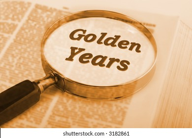 "Dictionary with magnifying glass emphasising the words ""Golden Years"". Concepts of  retirement, time to do what you want, fulfilment of dreams, relaxation, in warm sepia tone."