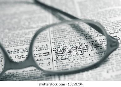 "Dictionary page focused on the word ""eyeglass"" through prescription eyeglasses."