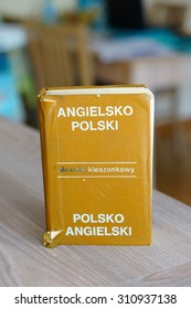 Dictionary in Polish and English language on wooden table