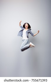 I did it! Dreams come true! Concept of freedom, happiness and life without problems. Vertical full length portrait of happy crazy woman is jumping up, isolated on grey background