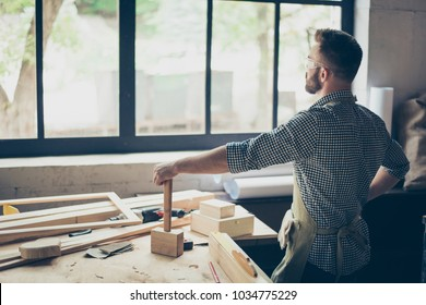 I did it! The task is complete! Rear behind view portrait of satisfied confident relaxed carpenter looking into the window and leaning on a wooden chisel, he is standing near desktop with instruments