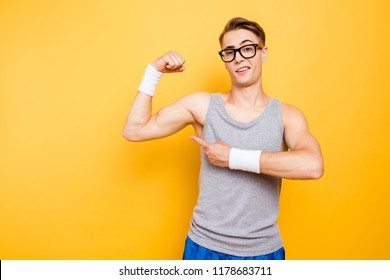 Did you see it? Portrait of funny youngster man show biceps on hand, arm isolated on bright yellow background