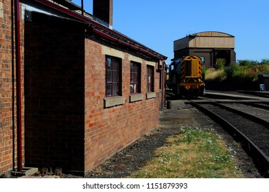 Didcot, Oxfordshire / UK - 08/05/2018: Engine shed (l), 1959 British Rail Class 08 diesel-electric shunter 08604 'Phantom' (centre) and Coal Stage building (r) at Didcot Railway Centre.