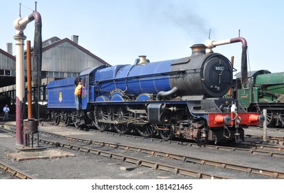 DIDCOT, UK - JULY 13. Preserved and restored vintage British GWR 4-6-0 steam locomotive 'King George II' 6023 in BR blue livery running on July 13, 2013 at Didcot Railway Centre, Oxfordshire, UK.