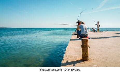 Didim, Turkey - October 03, 2017: Group of people fishing under the sun in Didim, Turkey. Leisure concept.