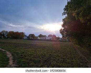 Die Sonne bricht durch die Wolken und erhellt das naturbehaftete Feld darunter.