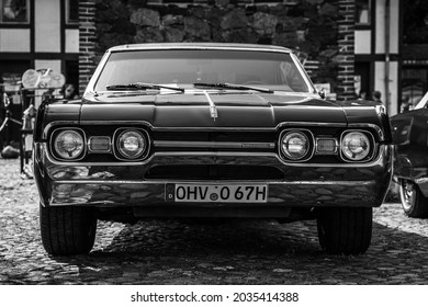 """DIEDERSDORF, GERMANY - AUGUST 21, 2021: The mid-size car Oldsmobile Cutlass Hardtop Coupe, 1967. Black and white. The exhibition of """"US Car Classics""""."""